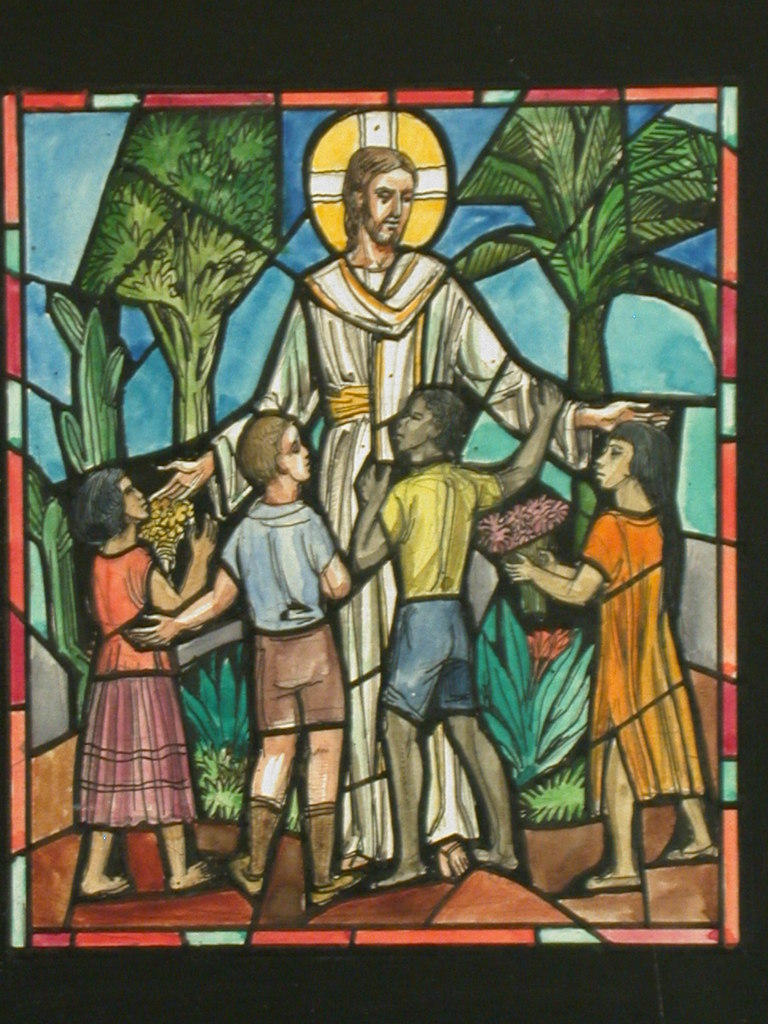 Stained glass image of Jesus blessing  children of different races.