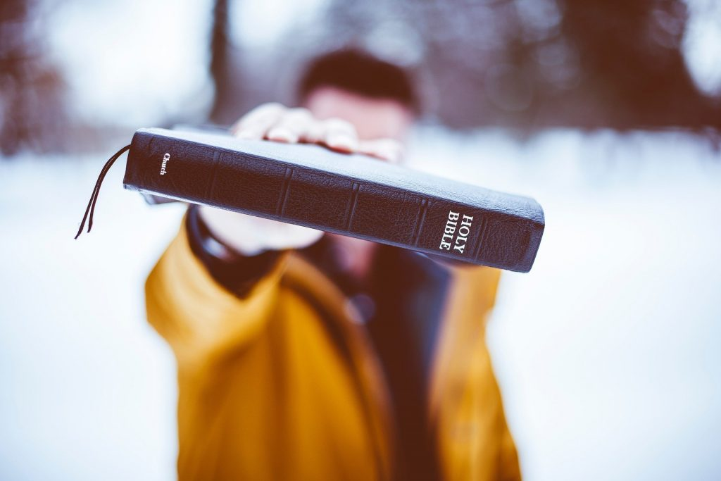 Man holding Bible in front of face.
